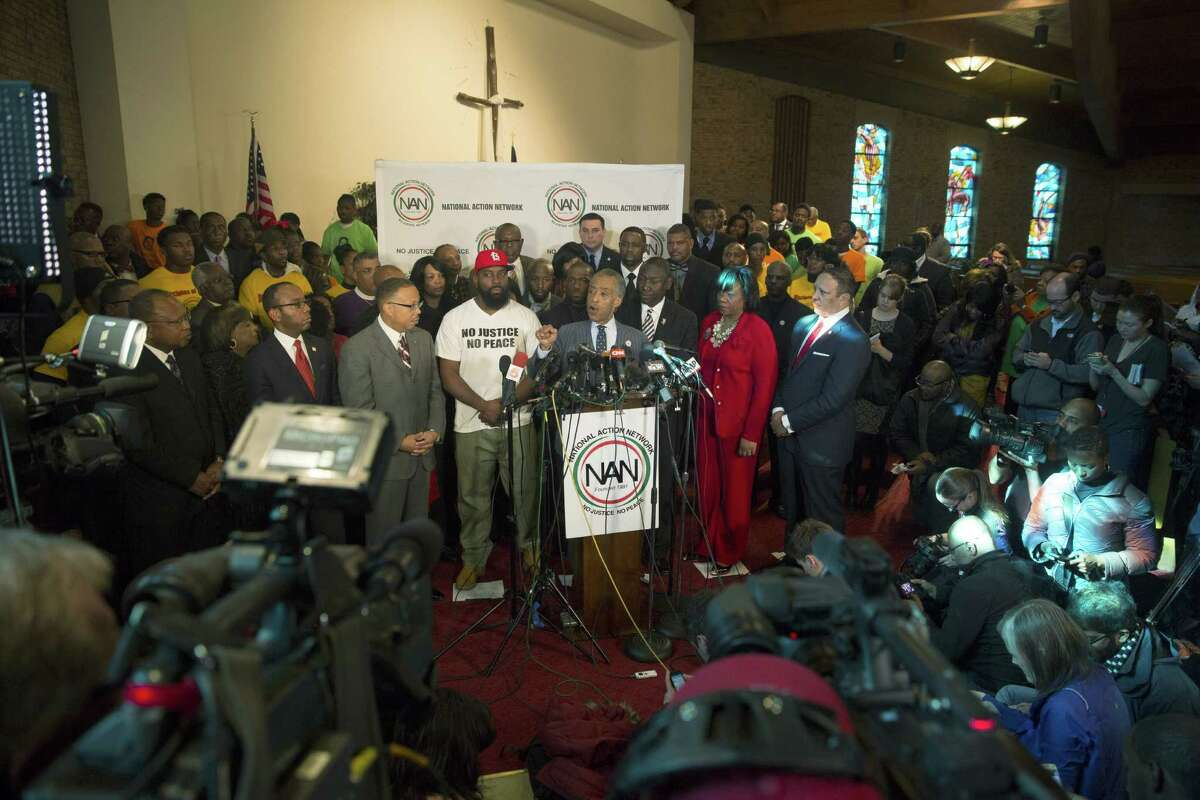 Rev. Al Sharpton, (center), speaks during a press conference at Greater St. Marks Church as Michael Brown Sr. (3rd left) and Brown family attorney Benjamin Crump (3rd right) look on.
