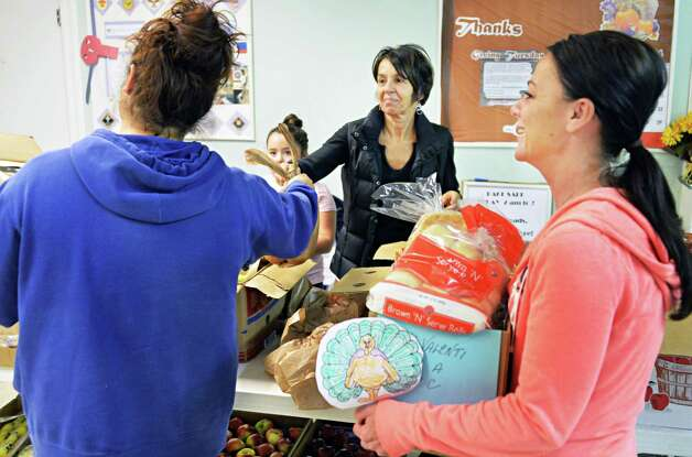 Volunteers Janice Bagarose and Nancy Perrotti, right, help a client during the holiday season at the Pawling Avenue Methodist Church Tuesday Nov. 25, 2014, in Troy, NY.  (John Carl D'Annibale / Times Union) Photo: John Carl D'Annibale / 00029600A