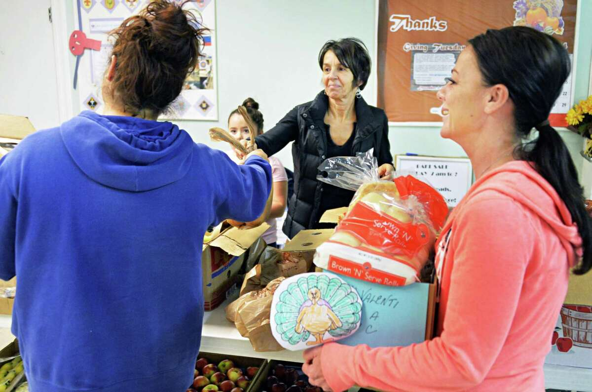 Volunteers Janice Bagarose and Nancy Perrotti, right, help a client during the holiday season at the Pawling Avenue Methodist Church Tuesday Nov. 25, 2014, in Troy, NY. (John Carl D'Annibale / Times Union)