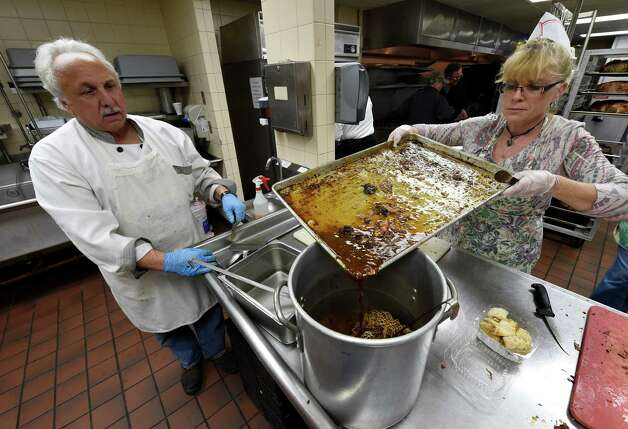 Chris Jones, left and Marie Parker work on the turkey gravy for the Thanksgiving Day Dinner Tuesday morning Nov. 25, 2014 at the Capital City Rescue Mission in Albany, N.Y.  The schedule of preparation was moved up due to the pending storm which may hit the area Wednesday.   (Skip Dickstein/Times Union) Photo: SKIP DICKSTEIN / 00029601A