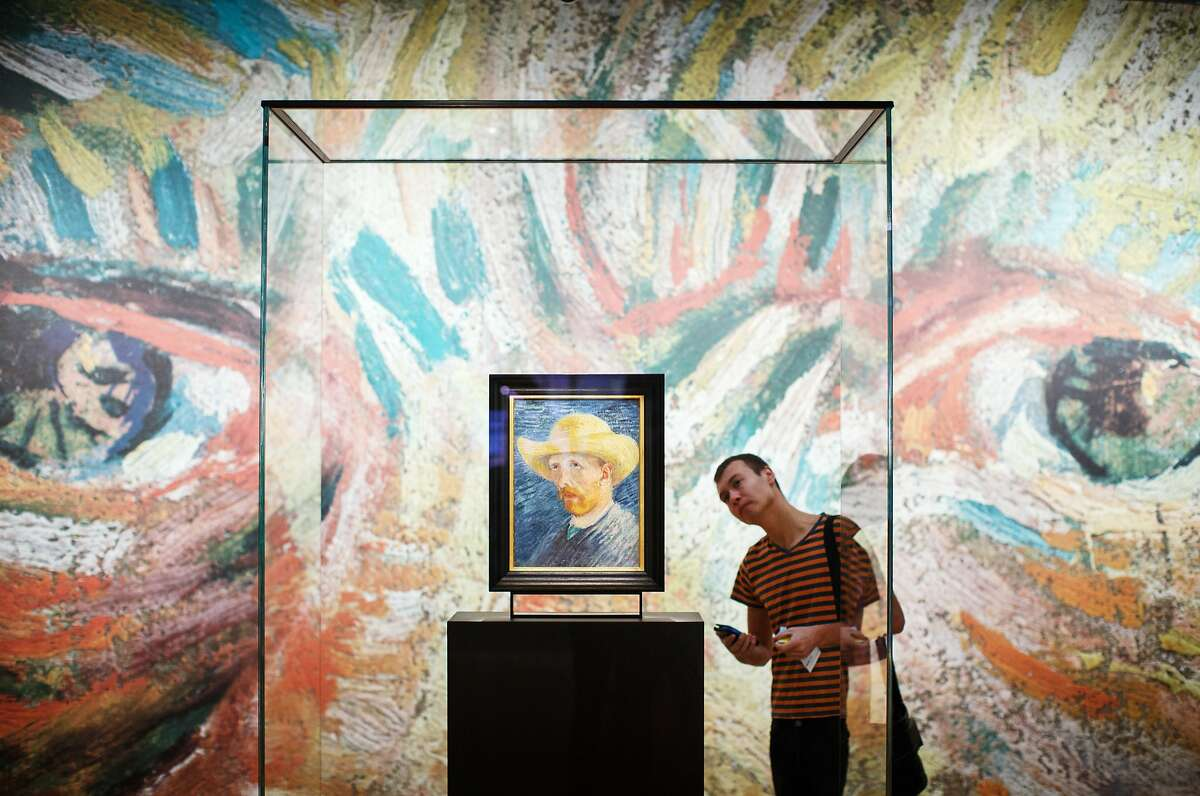 AMSTERDAM, NETHERLANDS - NOVEMBER 25: A visitor looks at a self portrait of Dutch Post-Impressionist painter Vincent van Gogh on the ground floor of the Vincent van Gogh museum on November 25, 2014 in Amsterdam, Netherlands. The new presentation of the permanent collection of Vincent van Gogh (1853-1890) works focuses on the development of the artist and the myths surrounding Van Gogh's suicide, illness and ear are discussed in detail for the first time at the museum. On the ground floor of the museum, visitor's first walk through an array of the Dutch artist's self-portraits. (Photo by Jasper Juinen/Getty Images) *** BESTPIX ***