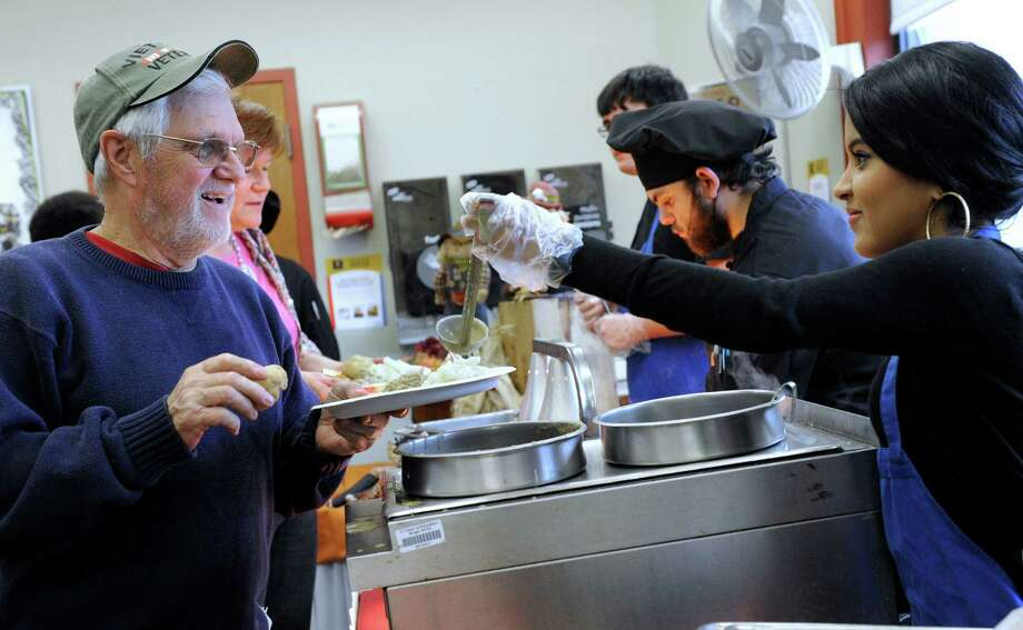 Jim Mead of Danbury, Conn., is served gravy for his turkey and mashed potatoes by Niesey Cruz, 15, during ACE's annual community Thanksgiving feast Tuesday, Nov. 25, 2014.  The Alternative Center for Excellence is in Danbury, Conn. Photo: Carol Kaliff / The News-Times