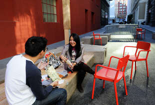Dan Chen (left) and Andrea Lee chat over lunch in the newly designed pedestrian-friendly plaza on Annie Street.