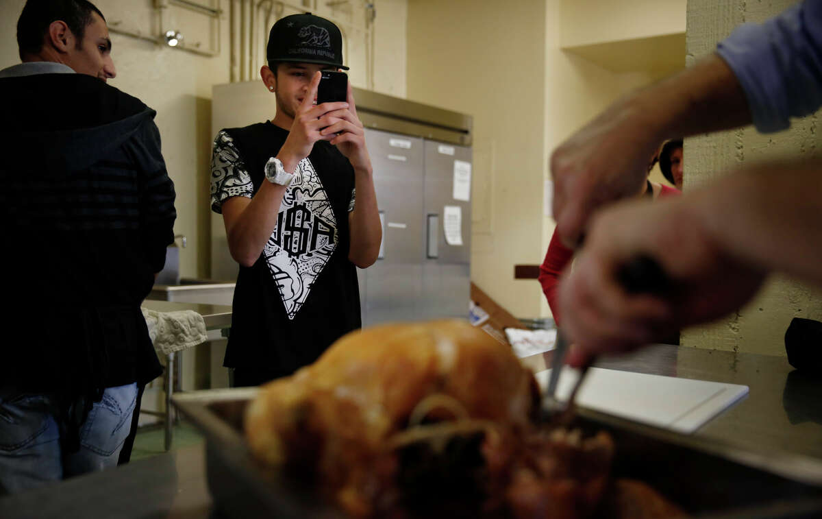 New student Andy Matamoros, 15, takes a photo as his Mission High School teacher Bill Wallace carves the turkey.