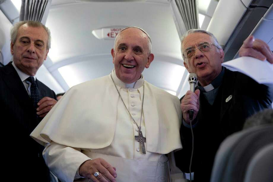 Pope Francis, flanked by Vatican spokesman father Federico Lombardi, first right, talks to journalists during a press conference he held aboard the papal flight on his way back from Strasbourg, eastern France, at the end of a one day visit to the European Parliament and Council, Tuesday, Nov. 25, 2014. Pope Francis has demanded Europe craft a unified and fair immigration policy, saying the thousands of refugees coming ashore need acceptance and assistance, not self-interested policies that risk lives and fuel social conflict. Francis made the comments Tuesday to the European Parliament during a brief visit meant to highlight his vision for Europe a quarter-century after St. John Paul II travelled to Strasbourg to address a continent still divided by the Iron Curtain. (AP Photo/Andrew Medichini) Photo: Andrew Medichini, STF / Associated Press / AP