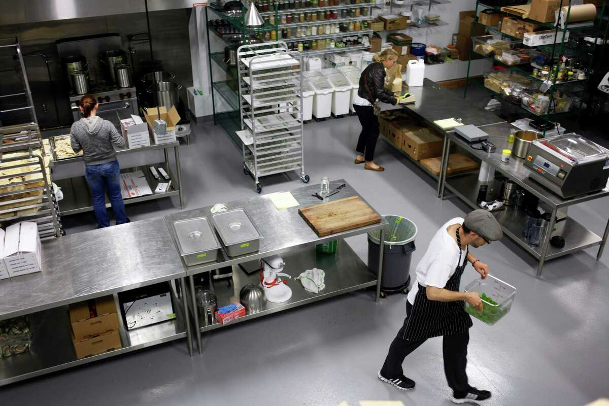 Chef Christian Phernetton carries a bin of food at the Mission: Heirloom Kitchen Lab in West Berkeley.