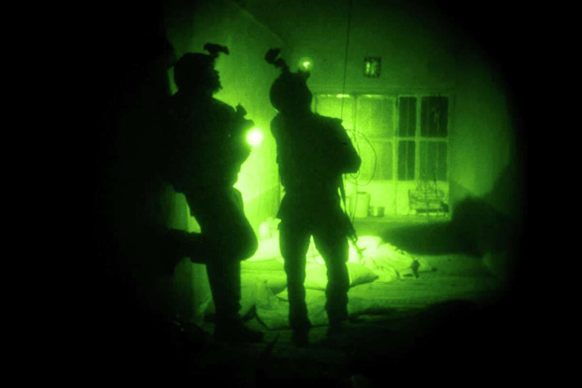 FILE - In this Oct. 28, 2009 file photo taken with a night vision scope, U.S. Special Operations forces search a home during a joint operation with Afghan National Army soldiers targeting insurgents operating in Afghanistan's Farah province. Afghan President Ashraf Ghani has ordered a top-to-bottom review of the practices of the country's defense forces, including discussing a possible resumption of controversial night raids banned by his predecessor, the Associated Press has learned. The move appears aimed at revamping the military for the fight against the Taliban amid new indications that U.S. and international forces will play a greater role than initially envisaged. (AP Photo/Maya Alleruzzo, File)