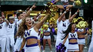 The University of Washington Cheerleading Squad performs during the Alaska Airlines Seafair Torchlight Parade on Saturday, July 26, 2014.  Thousands lined the streets to watch the parade which featured drill teams, marching bands, pirates, floats, and Sounders players Clint Dempsey and DeAndre Yedlin.