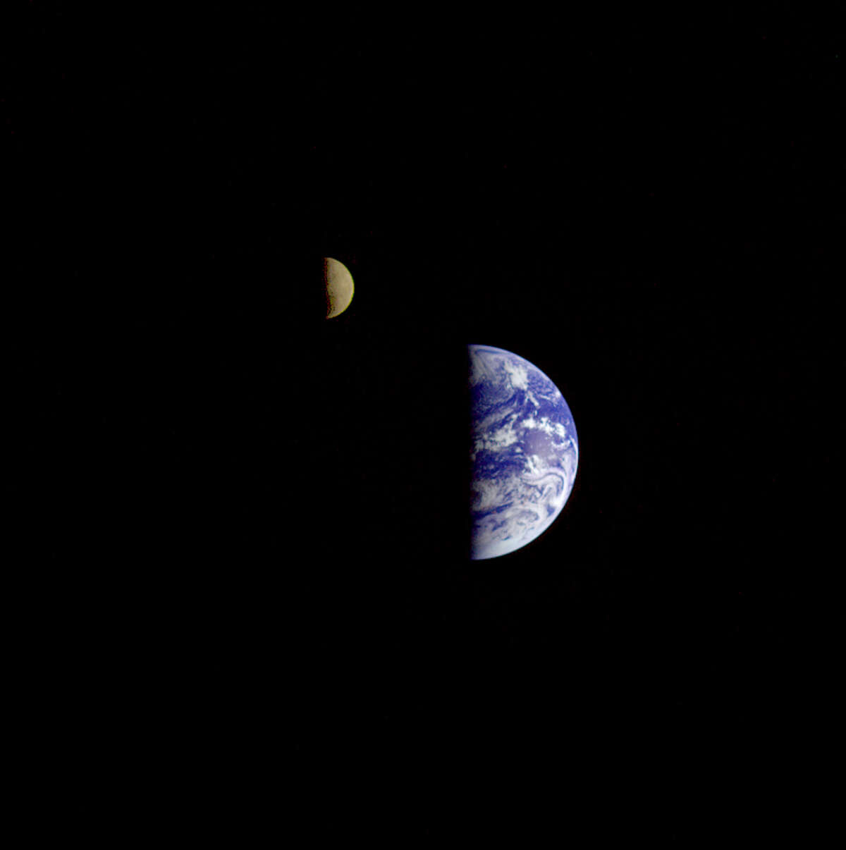 Eight days after its final encounter with the Earth, the Galileo spacecraft looked back and captured this remarkable view of the Earth and Moon. The image was taken from a distance of about 6.2 million km (3.9 million miles). The picture was made with images taken through the violet, red, and 1.0-micron infrared filters. The Moon is in the foreground, moving from left to right. The brightly-colored Earth contrasts strongly with the Moon, which reflects only about one-third as much sunlight as the Earth. Contrast and color have been computer-enhanced for both objects to improve visibility. Antarctica is visible through clouds (bottom). The Moon's far side is seen; the shadowy indentation in the dawn terminator is the south pole Aitken Basin, one of the largest and oldest lunar impact features.