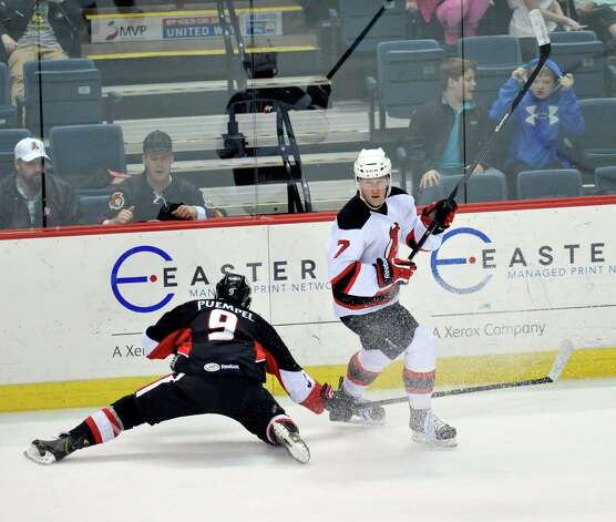 Albany Devils' Brandon Burlon (7) moves the puck past Binghamton Senators' Matt Puempel (9) during the first second period of an AHL hockey game in Albany, N.Y., Sunday, March 30, 2014. (Hans Pennink / Special to the Times Union) ORG XMIT: HP107 Photo: Hans Pennink / 00026292A
