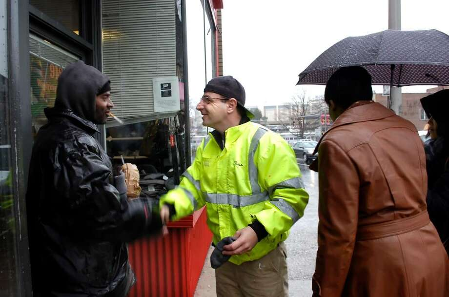 """Chris Comblo, center, gives out a hat and a pair of gloves to a man standing on Washington Blvd. in Stamford, Thursday morning, Feb. 25th, 2010.  Comblo runs a ministry called """"I Glove You"""", in which he gives out free hats and gloves to people on the street. Photo: Bob Luckey / Stamford Advocate"""
