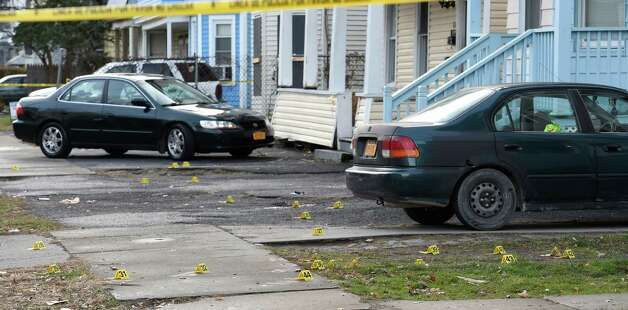 Numerous evidence markers are seen in front of 822-826 Bridge Street on  Nov. 25, 2014, as police secure the scene of a killing Monday in Schenectady, N.Y.     (Skip Dickstein/Times Union) Photo: SKIP DICKSTEIN