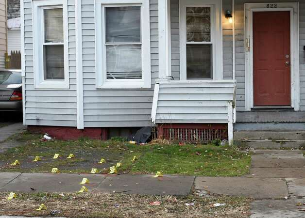 Numerous evidence markers are seen in front of 822 Bridge Street on  Nov. 25, 2014, as police secure the scene of a killing on Monday in Schenectady, N.Y.     (Skip Dickstein/Times Union) Photo: SKIP DICKSTEIN