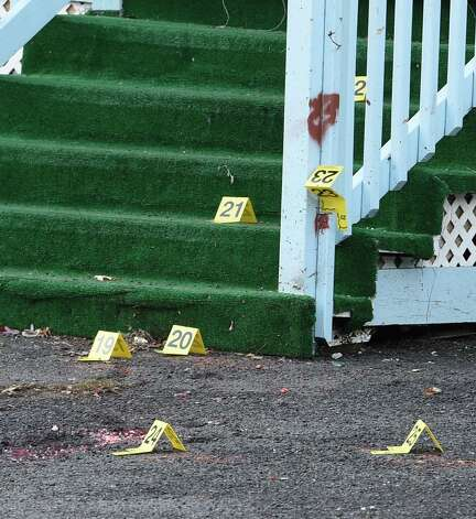 Numerous evidence markers are seen in front of 826 Bridge Street on  Nov. 25, 2014, as police secure the scene of a killing on Monday in Schenectady, N.Y.     (Skip Dickstein/Times Union) Photo: SKIP DICKSTEIN