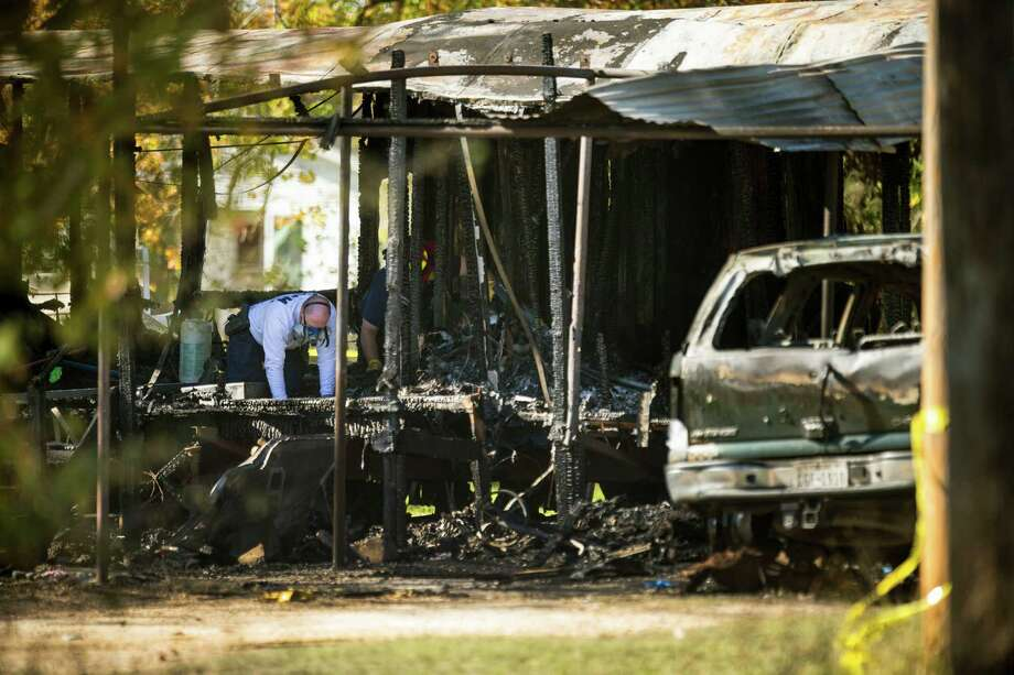 Investigators sift through a mobile home in Edna  that was destroyed by a fire that also killed five children between the ages of 5  and 15. Photo: Brett Coomer / Brett Coomer / Houston Chronicle / © 2014 Houston Chronicle