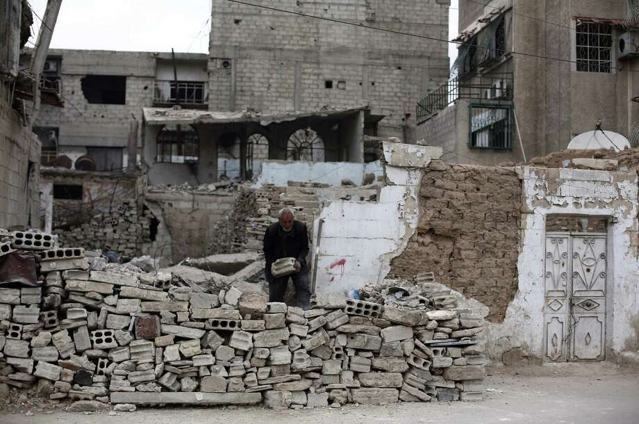Abu Hasan,  whose house was destroyed by an airstrike, builds a wall out of rubble in  Douma, Syria, northeast of Damascus. Photo: ABD DOUMANY, Stringer / AFP/Getty Images / AFP