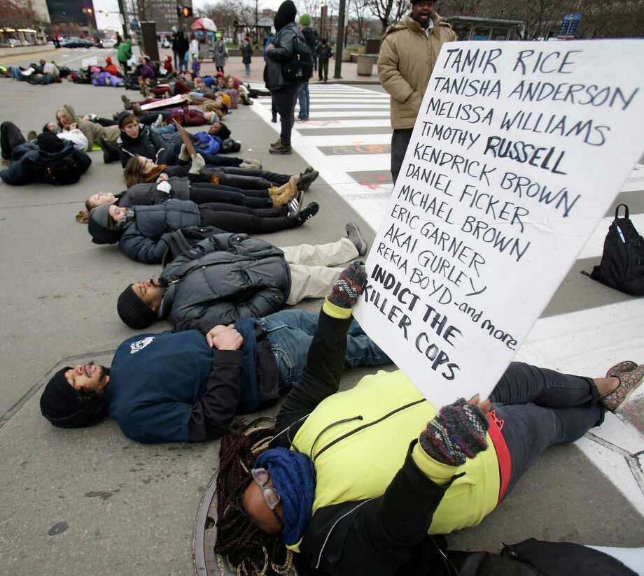 Demonstrators lay down in Public Square Tuesday, Nov. 25, 2014, in Cleveland, during a protest over the weekend police shooting of Tamir Rice. The 12-year-old was fatally shot by a Cleveland police officer Saturday after he reportedly pulled a replica gun at the city park. (AP Photo/Tony Dejak) Photo: Tony Dejak, STF / Associated Press / AP
