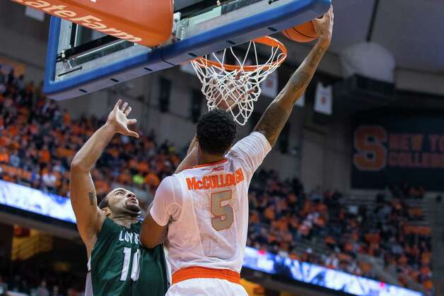 SYRACUSE, NY - NOVEMBER 25:  Chris McCullough #5 of the Syracuse Orange puts in the ball over the reach of Sean Tuohy Jr. #11 of the Loyola (MD) Greyhounds during the second half on November 25, 2014 at The Carrier Dome in Syracuse, New York. Syracuse defeats Loyola (MD) 70-37.  (Photo by Brett Carlsen/Getty Images) ORG XMIT: 521825415 Photo: Brett Carlsen / 2014 Getty Images
