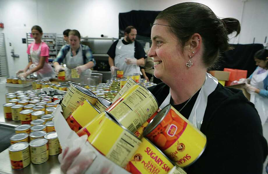 Whitney Watson carries cans of yams, who with other members of her family opened drained and mashed them in pans in preparation for The Jimenez Thanksgiving Dinner at the Henry B. Gonzalez Convention Center.  Its the first year for the group to volunteer.  Tuesday, Nov. 25, 2014. Photo: BOB OWEN, San Antonio Express-News / © 2014 San Antonio Express-News