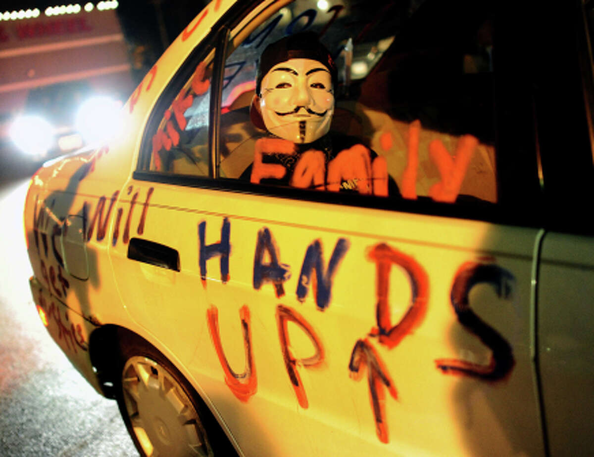 A protestor sits in the back of a car outside the Ferguson police station on Tuesday, Nov. 25, 2014, in the wake of the grand jury decision not to indict officer Darren Wilson in the shooting death of Ferguson, Mo., teen Michael Brown. (Wally Skalij/Los Angeles Times/TNS)