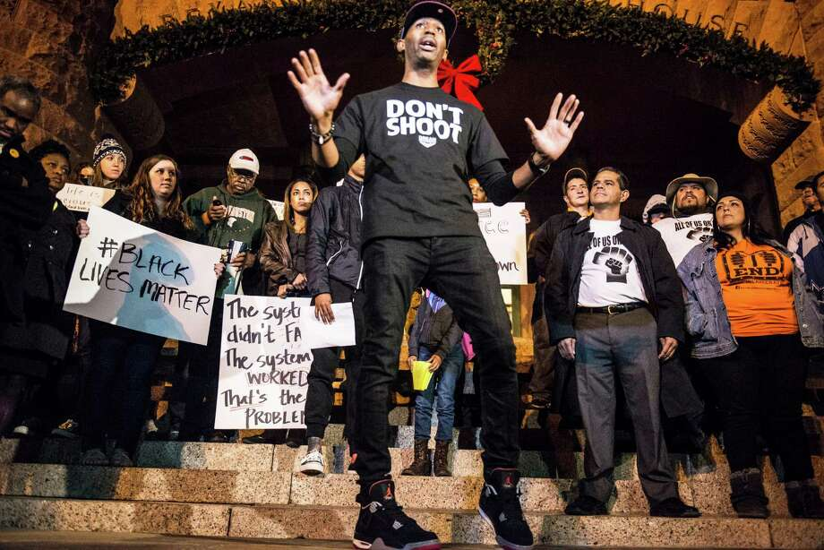 Protesters led by SATX4Ferguson leader Mike Lowe (center) gather at the Bexar County Courthouse in San Antonio on Tuesday, November 25, 2014, to protest the St. Louis County Grand Jury's decision not to indict Ferguson Police Officer Darren Wilson after he shot and killed unarmed teenager Michael Brown in Ferguson, Missouri, in August. The grand jury's decision was announced Monday night and has led to protests across the country. Photo: Matthew Busch, For San Antonio Express-News / © Matthew Busch