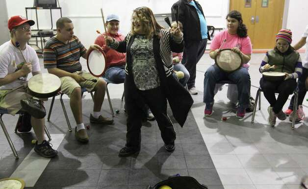 "Sandra Hernandez reacts with joy after leading a drum circle at The ARC of San Antonio on Tuesday, Nov. 25, 2014. Occupational therapist and drum circle facilitator Jorge Ochoa led the group of individuals with special needs in a percussion jam session. On the fourth Tuesday of each month Ochoa brings out several percussion instruments for his musicians to play. Many in the group have cerebral palsy, autism or down syndrome. Ochoa started doing drum circles with special needs individuals in 2008 and believes the sessions help each person in developing good social skills and emotional control. ""It (the drum circles) is about creativity and self-expression. People can come and have a good time, relieve some stress and express themselves. My emphasis is I want everybody to be involved. I don't want to leave anybody out. I feel like I'm blessed to give them the opportunity to experience something like this,"" Ochoa said. The drum circles are conducted in partnership with Eva's Heroes and The ARC of San Antonio. Photo: Kin Man Hui, San Antonio Express-News / ©2014 San Antonio Express-News"