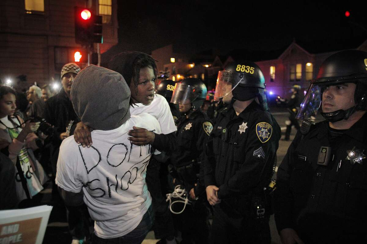 Tina and her son Pharoah, walk up near the line of police at Jackson Street and 6th Street where protesters tried to get to the on ramp to highway 880 during local protests about Ferguson Police shooting of Michael Brown on Tuesday, November 25, 2014, in Oakland, Calif.
