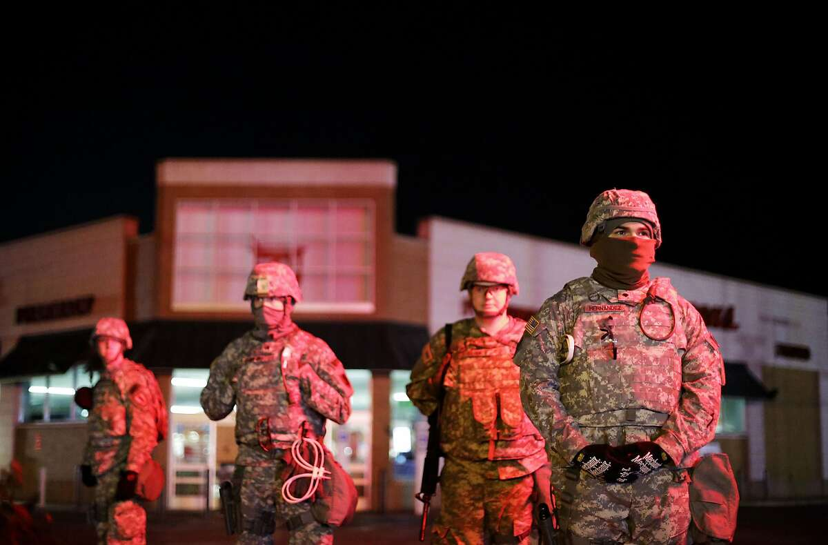 Missouri National Guard stand watch outside a Walgreens store, Wednesday, Nov. 26, 2014, in Ferguson, Mo. Missouri's governor ordered hundreds more state militia into Ferguson on Tuesday, after a night of protests and rioting over a grand jury's decision not to indict police officer Darren Wilson in the fatal shooting of Michael Brown, a case that has inflamed racial tensions in the U.S.