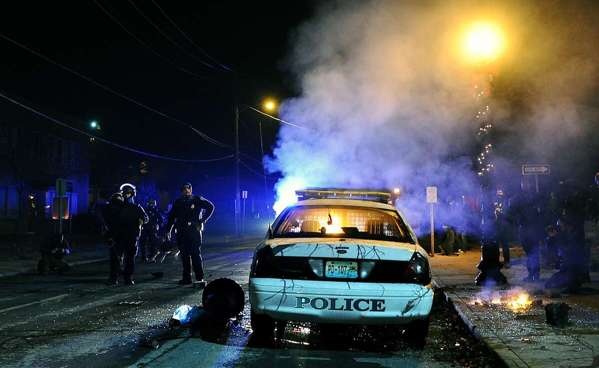 A police vehicle burns after being set by protestors in front of Ferguson City Hall on Tuesday, Nov. 25, 2014, in the wake of the grand jury decision not to indict officer Darren Wilson in the shooting death of Ferguson, Mo., teen Michael Brown.