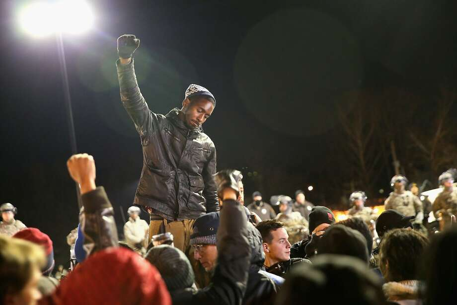 Demonstrators protest outside the Ferguson police station as soldiers with the Missouri National Guard stand watch on November 25, 2014 in Ferguson, Missouri. Yesterday rioting erupted following the grand jury announcement to not indict officer Darren Wilson in the Michael Brown case.  Brown, an 18-year-old black man, was killed by Darren Wilson, a white Ferguson police officer, on August 9. At least 12 buildings were torched and more than 50 people were arrested during the night-long rioting. Photo: Scott Olson, Getty Images