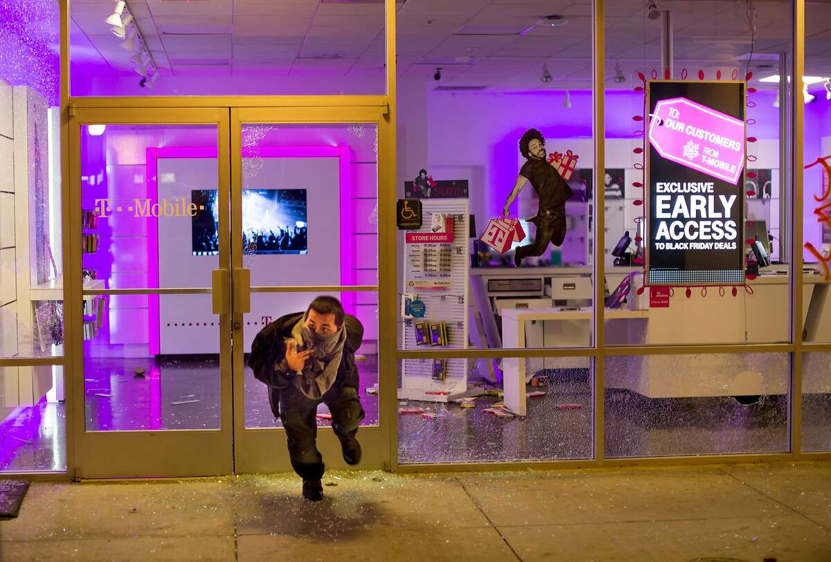 A man leaves a looted T-Mobile store in Oakland, Calif., on Tuesday, Nov. 25, 2014, a day after the announcement that a grand jury decided not to indict Ferguson police officer Darren Wilson in the fatal shooting of Michael Brown. Protesters briefly shut down two major freeways, vandalized police cars and looted businesses in downtown Oakland, smashing windows at cell phone stores, car dealerships, restaurants and convenience stores on a second night of protests.