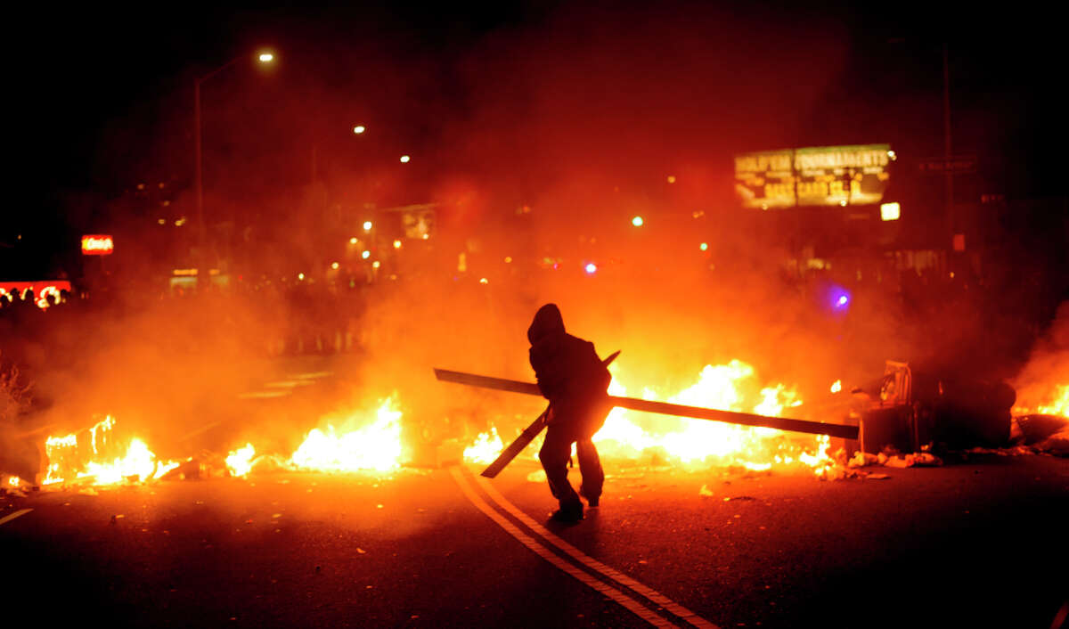 A protester adds wood to a fire burning in Oakland on Tuesday night.