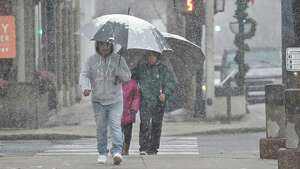 Pedestrians use umbrellas to keep themselves dry as a wet snow falls in downtown Danbury on Wednesday morning. The National Weather Service has issued a Winter Storm Warning for November 26 & 27, calling for snow during the day on Wednesday, changing to rain and snow Wednesday night with rain and snow showers on Thanksgiving day. Wednesday, November 26, 2014, Danbury, Conn.