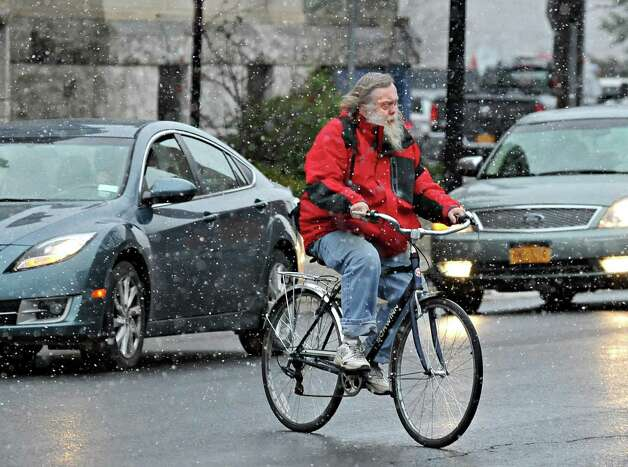 Randy Smeltzer rides his bike to the Post Office as snow begins to fall Wednesday morning Nov. 26, 2014, in Cohoes, NY.  (John Carl D'Annibale / Times Union) Photo: John Carl D'Annibale / 00029647A