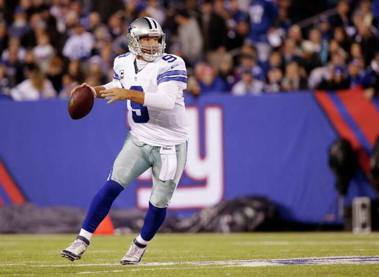 Dallas Cowboys quarterback Tony Romo (9) rolls out of the pocket to pass against the New York Gia