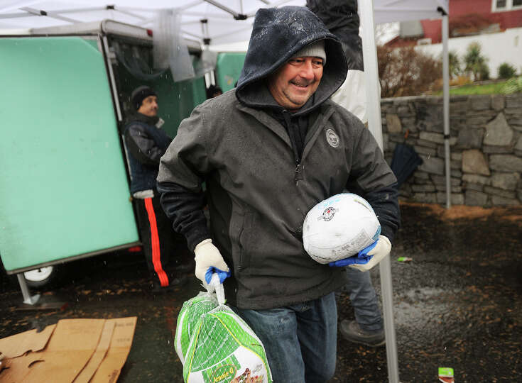 Vassos Vassiliou, a volunteer from St. Michael's Church in Greenwich, carries turkeys to the waiting