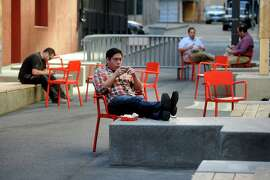 Brandon Espinosa checks his phone in the new plaza on Annie Street.
