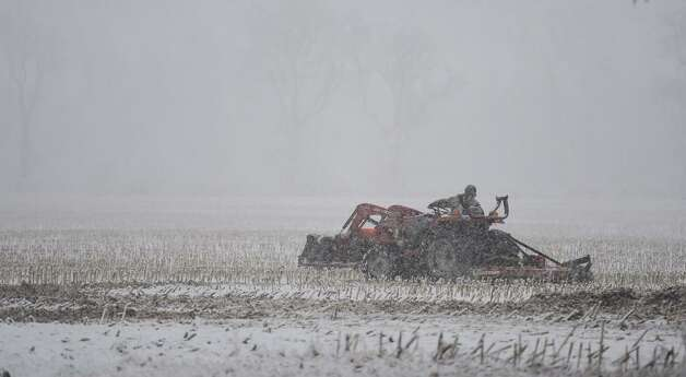 A farmer works his cornfield for the final time this fall as snow comes down in Stuyvesant, Columbia County, on Wednesday, Nov. 25, 2014. (Skip Dickstein/Times Union)