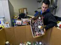 Cosmo Iadanza sorts new food donations at the Food Bank of Lower Fairfield County in Stamford, Conn., on Wednesday, November 26, 2014.