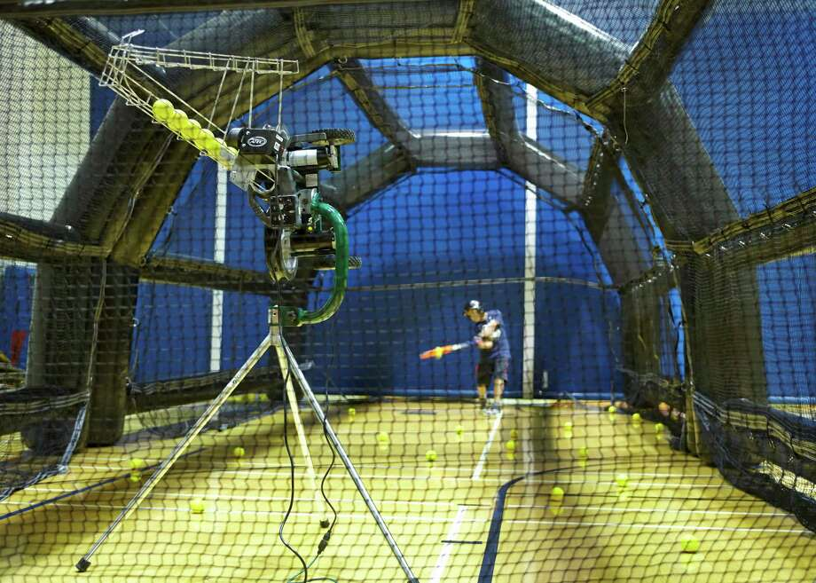 The new pitching machine at YWCA Greenwich throws curves, sliders, changeups, and fastballs up to 95 mph. Photo: Contributed Photo / Greenwich Time Contributed