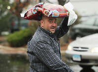 A man uses a bag of dry dog food to protect himself from the rain outside Stop & Shop on the Post Road in Milford, Conn. on Wednesday, November 26, 2014.