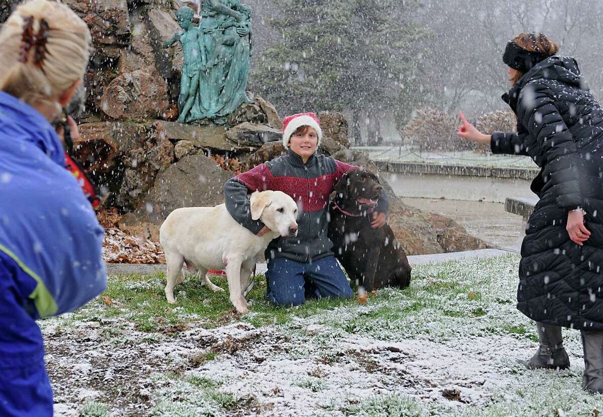 Jackie Nichols takes a photo of her nephew Reagan Lyon, 11, and his dogs Alistair and Baxter as Reagan's mother Jennifer Imire tries to get the dogs to behave in Washington Park during a snow storm on Wednesday, Nov. 26, 2014 in Albany, N.Y. The family from Glens Falls was trying out a new location to take their Christmas card photos. (Lori Van Buren / Times Union)