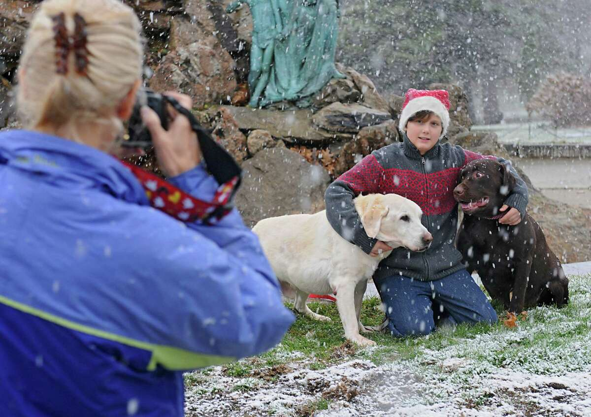Jackie Nichols takes a photo of her nephew Reagan Lyon, 11, and his dogs Alistair, left, and Baxter in Washington Park during a snow storm on Wednesday, Nov. 26, 2014 in Albany, N.Y. The family from Glens Falls was trying out a new location to take their Christmas card photos. (Lori Van Buren / Times Union)
