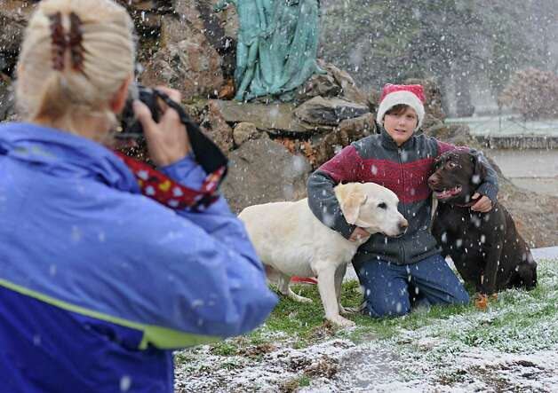 Jackie Nichols takes a photo of her nephew Reagan Lyon, 11, and his dogs Alistair, left, and Baxter in Washington Park during a snow storm on Wednesday, Nov. 26, 2014 in Albany, N.Y. The family from Glens Falls was trying out a new location to take their Christmas card photos.  (Lori Van Buren / Times Union) Photo: Lori Van Buren / 00029647A