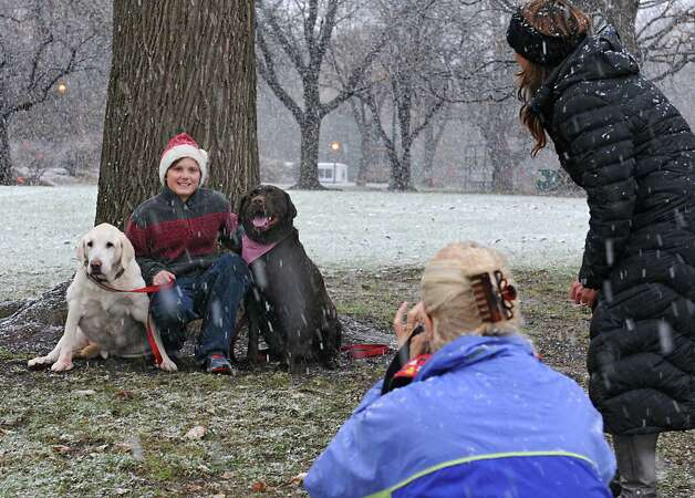 Jackie Nichols takes a photo of her nephew Reagan Lyon, 11, and his dogs Alistair and Baxter as Reagan's mother Jennifer Imire, right, tries to get the dogs to look in her direction in Washington Park during a snow storm on Wednesday, Nov. 26, 2014 in Albany, N.Y. The family from Glens Falls was trying out a new location to take their Christmas card photos.  (Lori Van Buren / Times Union) Photo: Lori  Van Buren / 00029647A