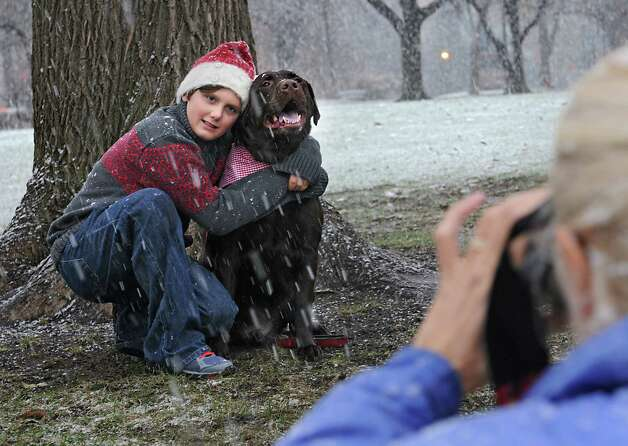 Jackie Nichols takes a photo of her nephew Reagan Lyon, 11, with his dog Baxter in Washington Park during a snow storm on Wednesday, Nov. 26, 2014 in Albany, N.Y. The family from Glens Falls was trying out a new location to take their Christmas card photos.  (Lori Van Buren / Times Union) Photo: Lori Van Buren / 00029647A