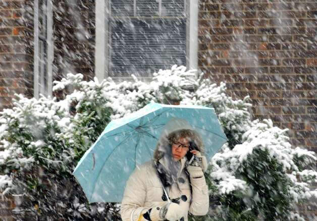 As snow falls UAlbany student Qixuan Loki Lio waits for a bus on Wasington Avenue Wednesday Nov. 26, 2014 in Albany, N.Y. (Michael P. Farrell/Times Union) Photo: Michael P. Farrell / 00029647A