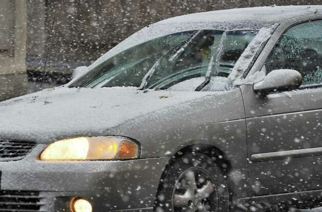 A car navigates down State St. as snow falls Wednesday Nov. 26, 2014, in Troy, NY.  (John Carl D'Annibale / Times Union) Photo: John Carl D'Annibale / 00029647A