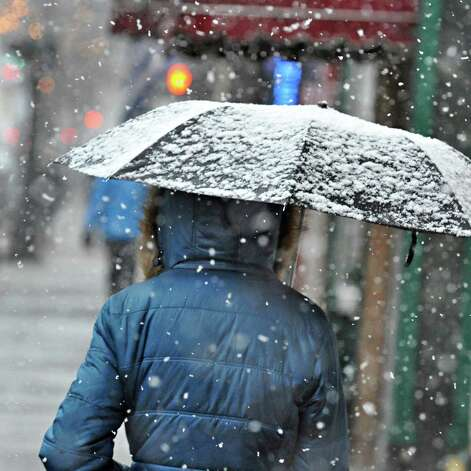 A heavy wet snow coats the umbrella of a pedestrian  Wednesday Nov. 26, 2014, in downtown Troy, NY.  (John Carl D'Annibale / Times Union) Photo: John Carl D'Annibale / 00029647A