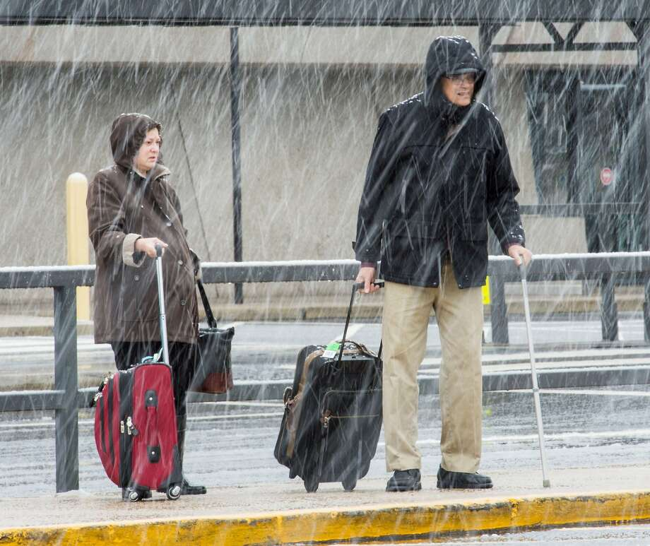 """Airline passengers at Dulles International Airport outside Washington, DC,  in Virginia, arrive to snow showers on the busiest travel day of the year November 26, 2014. Hundreds of flights were cancelled or delayed Wednesday in the US northeast as a winter storm delivered freezing rain and snow ahead of the Thanksgiving holiday, one of the year's biggest travel weekends. A wintry mix was falling in Boston, Philadelphia, New York and Washington, according to the National Weather Service, which forecast """"havoc"""" for travelers along the east coast from the Carolinas up through New England. Photo: Paul J. Richards, AFP/Getty Images"""